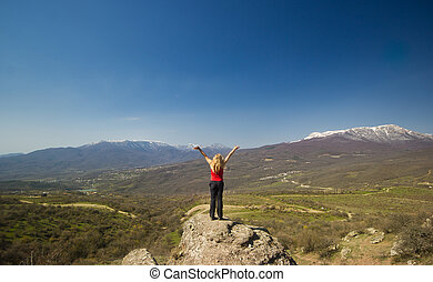 girl with hands up in the mountains against sun