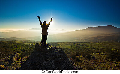 girl with hands up in the mountsins against sun