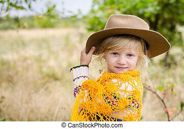 girl with hat and orange pelerine in autumn season