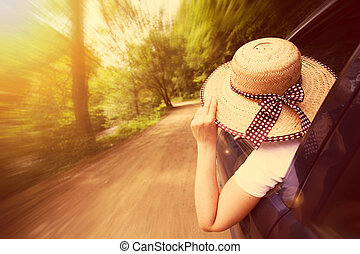 Girl with hat in the window of the car
