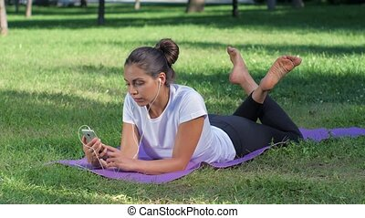 Girl with headphones and with the phone in her hand lying on the yoga mat