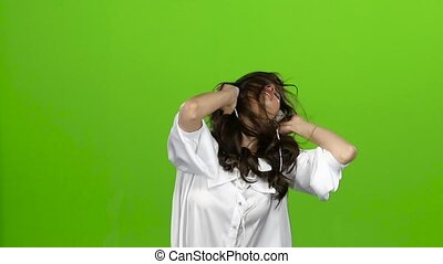 Girl with headphones in her ears, waving her head in different directions, she loves music. Green screen. Slow motion