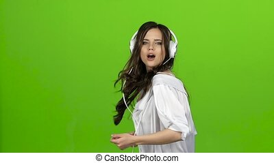 Girl with headphones in her ears whirls in dance she loves music. Green screen. Slow motion
