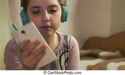Girl with headphones listening music from smartphone