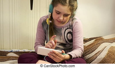 Girl with headphones listening to music from smartphone