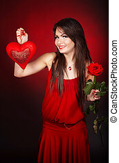 Girl with  heart and flower rose on red  background.