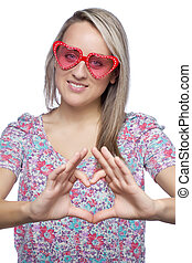 girl with heart-shape sunglasses making heart sign