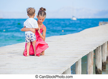 Girl with her brother walking on jetty
