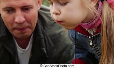 girl with her dad is outside in park blows candle celebrating the fifth year of her birthday with cake in slowmotion.