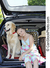 Girl with her dog in a car