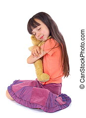 A young girl sits down, closing her eyes and smiling slightly as she hugs her favourite toy close.