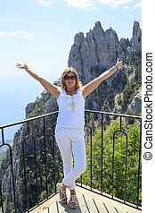 girl with her hands up stands on top of mountain