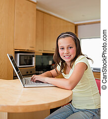 Girl with her laptop at the kitchen table