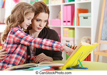 girl with her mother doing homework at home