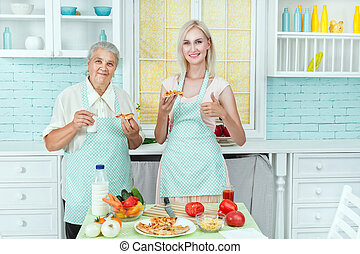 Girl with her mother in the kitchen.