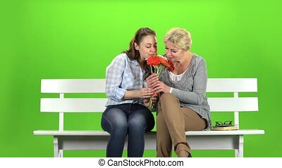 Girl with her mother is sniffing a bouquet of flowers. Green screen