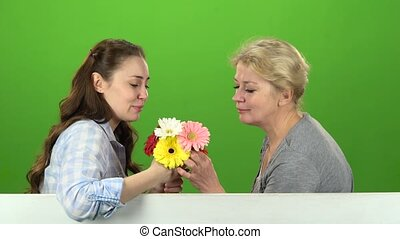 Girl with her mother is sniffing a bouquet of flowers. Green screen. Side view