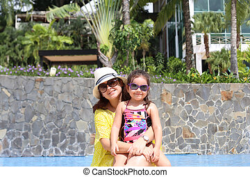 Girl with her mother outside swimming pool enjoying the summerwi