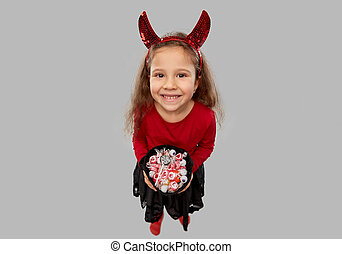 girl with horns trick-or-treating on halloween