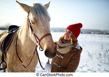 Happy girl in winterwear looking at horse in rural environment