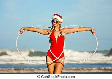 Girl with hula hoops on the beach