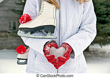 Girl with ice skates and ice heart with red gloves.