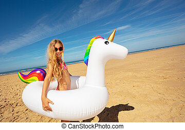 Girl with inflatable toy unicorn on sea beach