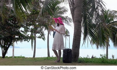 Girl with ipad and bagage in the palm forest near sea