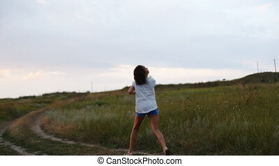 Girl with kite running on road