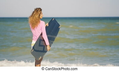 Girl with kiteboard is walking along the beach tropical...