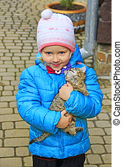 Girl with kitten in arms. Children love for animals. Favorite pet.
