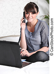 Girl with laptop and phone sitting on her bed
