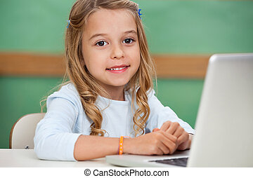 Girl With Laptop At Classroom Desk