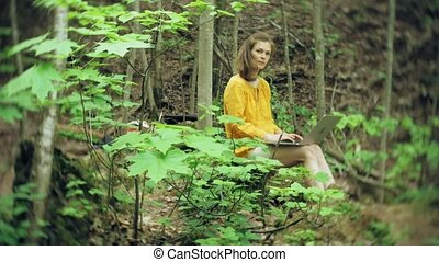 Girl with Laptop, Sitting On a Rock, In the Forest