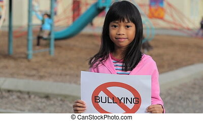 Girl With Large NO BULLYING sign - A cute Asian girl holds...