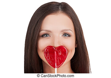 Girl with lollipop. Portrait of beautiful young woman holding heart shape lollipop in front of her lips while isolated on white