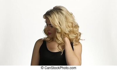 Girl with long blond hair. Beautiful hair curls. White. Slow motion