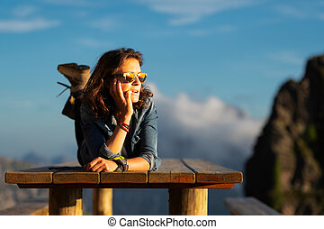 Girl with long Caucasian hair on a wooden table outside an alpine hut during a trek
