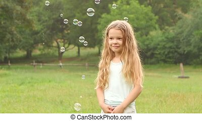 Girl with long curly hair looking at soap bubbles in the garden on a background of trees. Slow motion