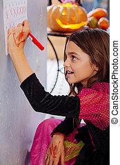 Girl with long dark hair wearing Halloween dress crossing dates in calendar