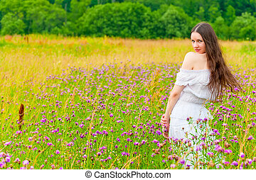 girl with long hair in a field with purple flowers