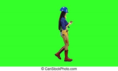Girl with long hair in a helmet goes sideways on green background