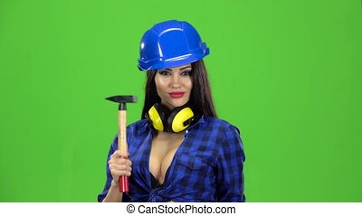 Girl with long hair in a helmet holding hammer and knocking them on hand on green background