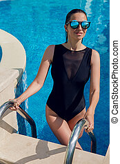 girl with long hair in one-piece swimsuit and sunglasses