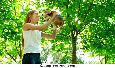 girl with long hair playing with her beagle dog in park. Slow motion