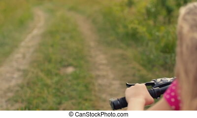 girl with long hair rides a bicycle on a grassy road