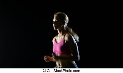 Girl with long hair runs confidently on a black background. Close up