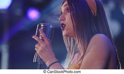 Girl with long hair sings to retro microphone