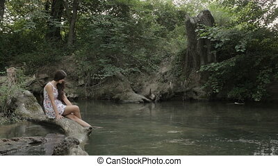 Girl with long hair sitting on a log and wets feet in the water of the river