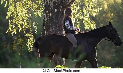 Girl with long hair walks on horseback around the tree in...